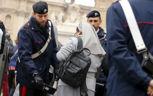 Italian Carabinieri officers check a nun as she arrives to attend Pope Francis' Wednesday general audience in St. Peter's Square at the Vatican. (Photo courtesy Reuters/Tony Gentile.)